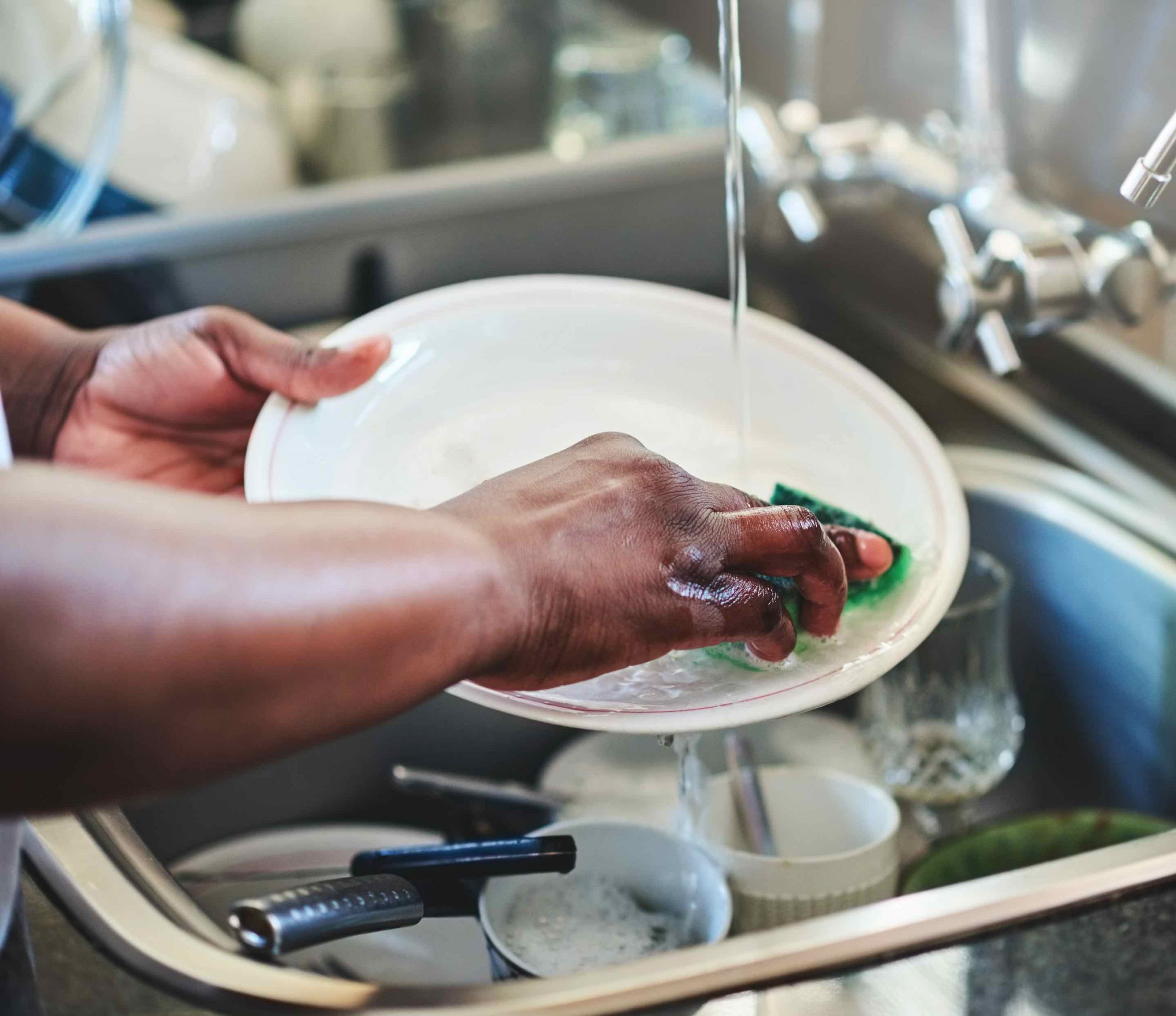 Woman scrubbing dishes overtop kitchen sink with Plant-Based Dish Soap