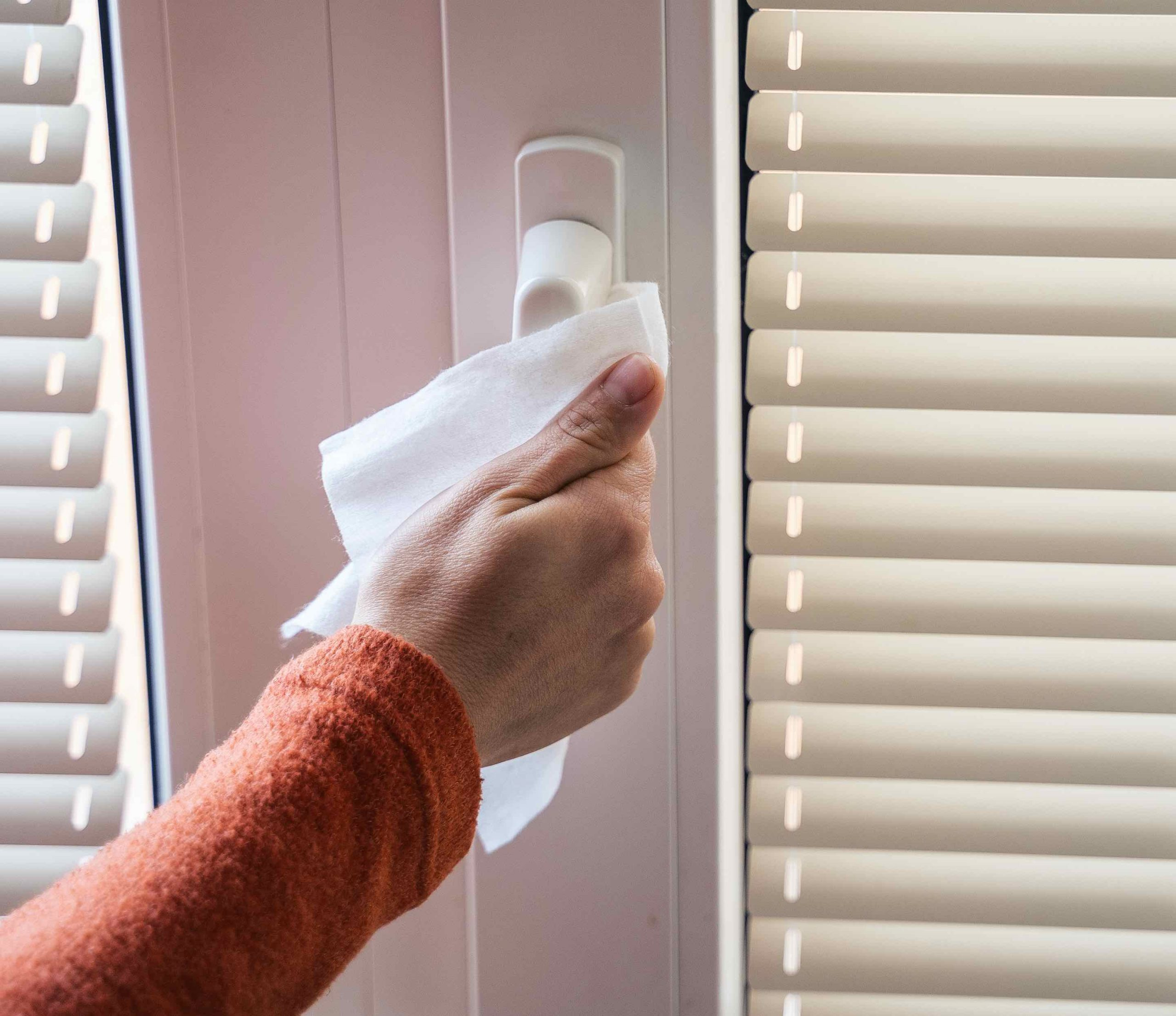 Woman disinfecting door handle with Non-Toxic Cleaning Wipes