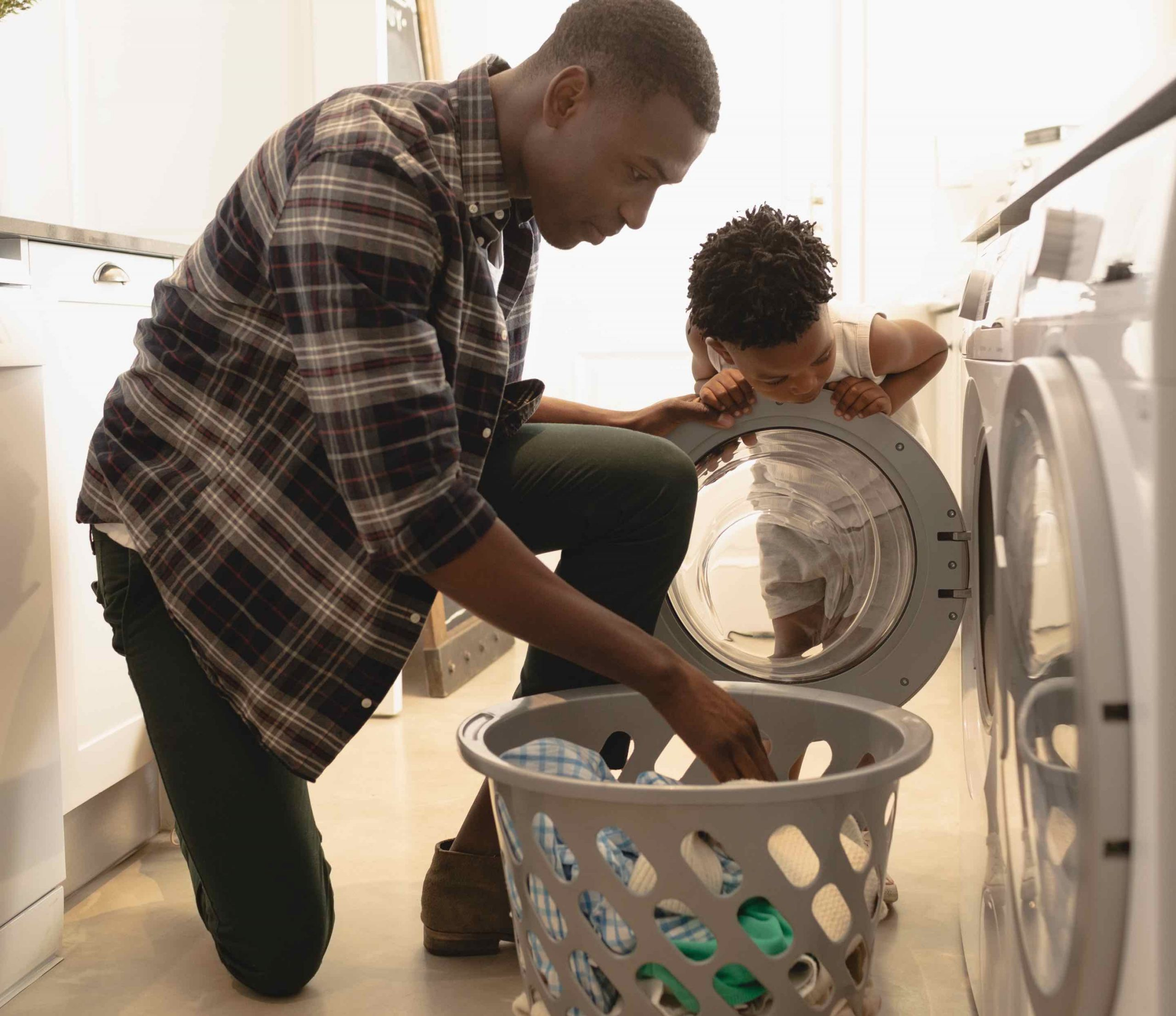 Father and son loading laundry using Plant-Based Laundry Detergent