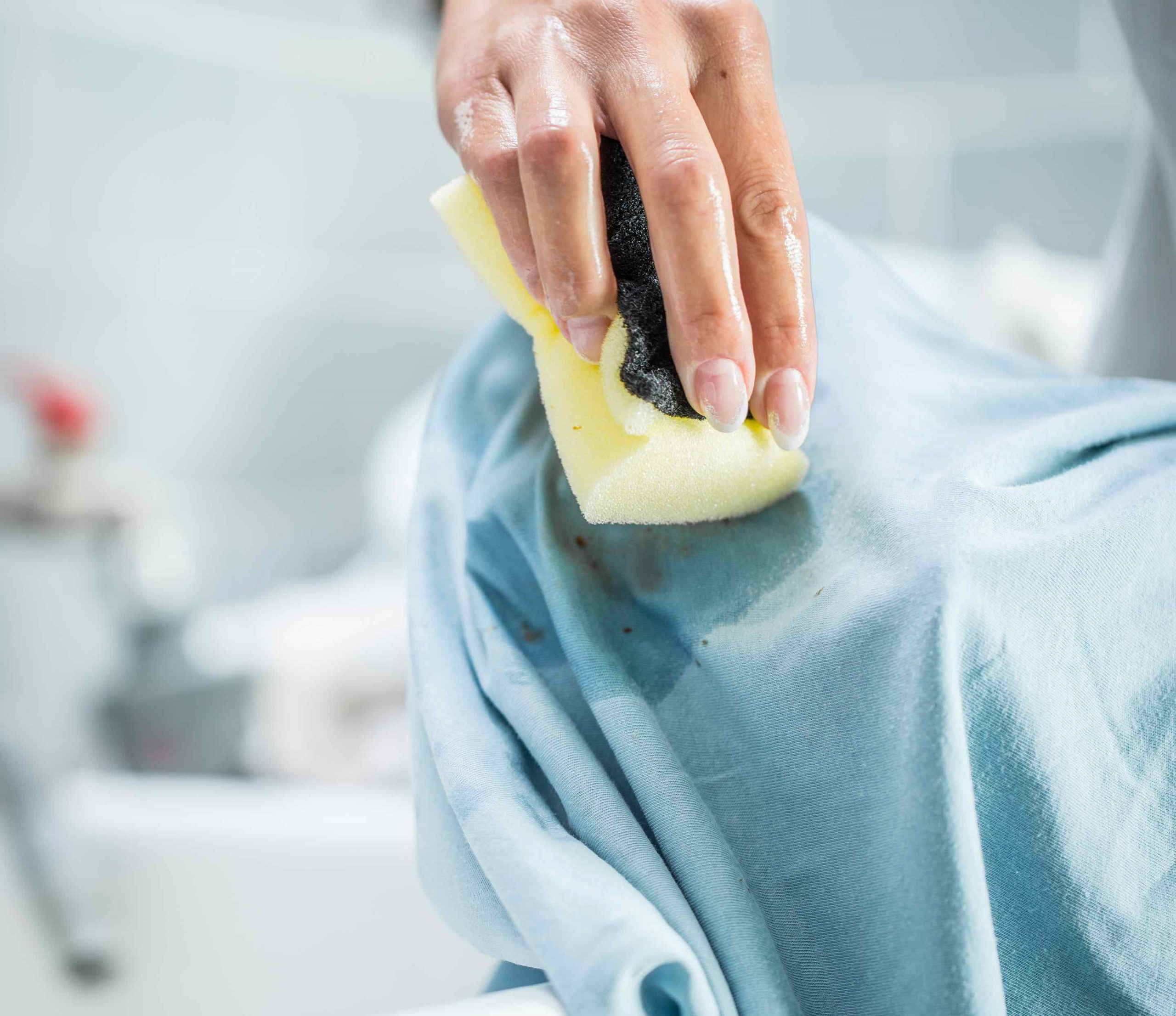 Woman scrubbing stain out of a shirt with Plant-Based Stain Remover